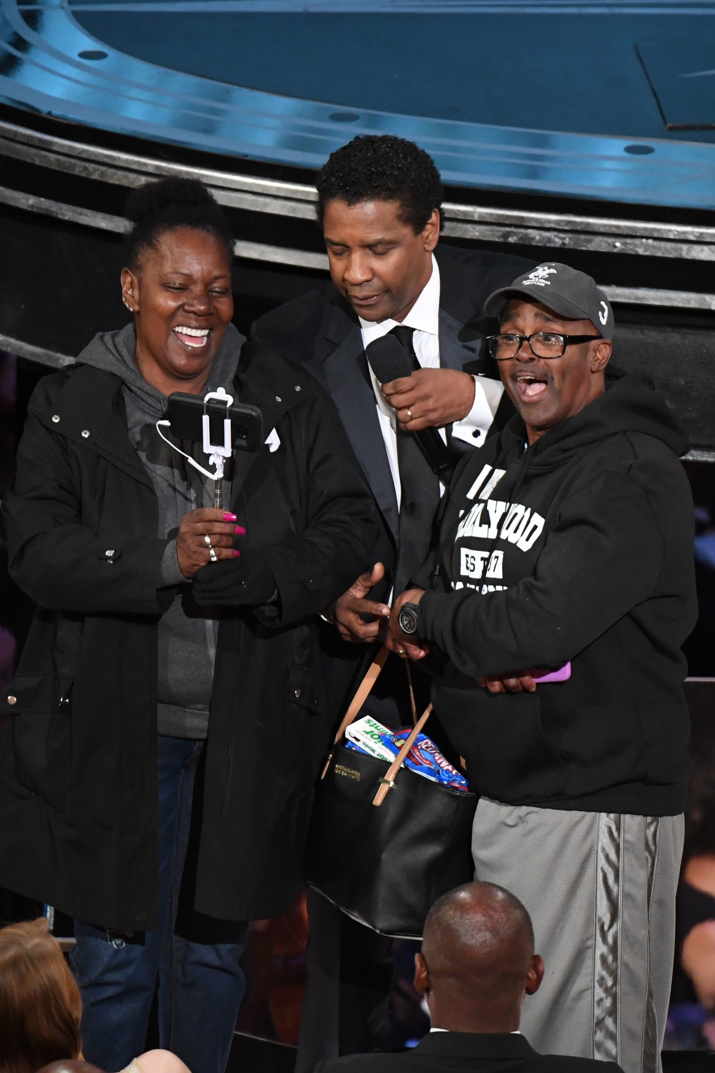 Tourists brought into the Oscars as a surprise meet with nominee for Best Actor in 'Fences' Denzel Washington (C) at the 89th Oscars on February 26, 2017 in Hollywood, California. / AFP / Mark RALSTON        (Photo credit should read MARK RALSTON/AFP/Getty Images)