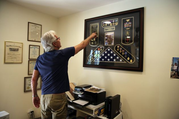 Owens points to a display of his son's medals and