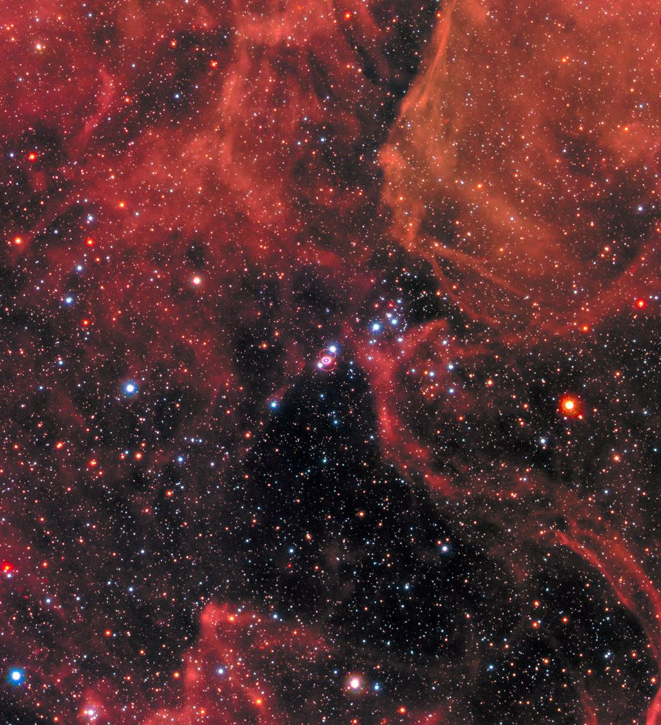 SN 1987A can be seen at the centre of this image, resembling a white eye with a bright white pupil. The...