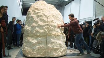 French artist Abraham Poincheval (inside the stone) performs 'Pierre' (Stone), at the Palais de Tokyo on February 22, 2017 in Paris. A French artist was entombed on February 22, 2017 inside a 12-tonne boulder for a week, saying: 'I think I can take it.' With the world's press looking on, the two halves of the limestone rock were closed on Abraham Poincheval by workmen in a Paris modern art museum.  / AFP / JOEL SAGET / RESTRICTED TO EDITORIAL USE - MANDATORY MENTION OF THE ARTIST UPON PUBLICATION - TO ILLUSTRATE THE EVENT AS SPECIFIED IN THE CAPTION        (Photo credit should read JOEL SAGET/AFP/Getty Images)