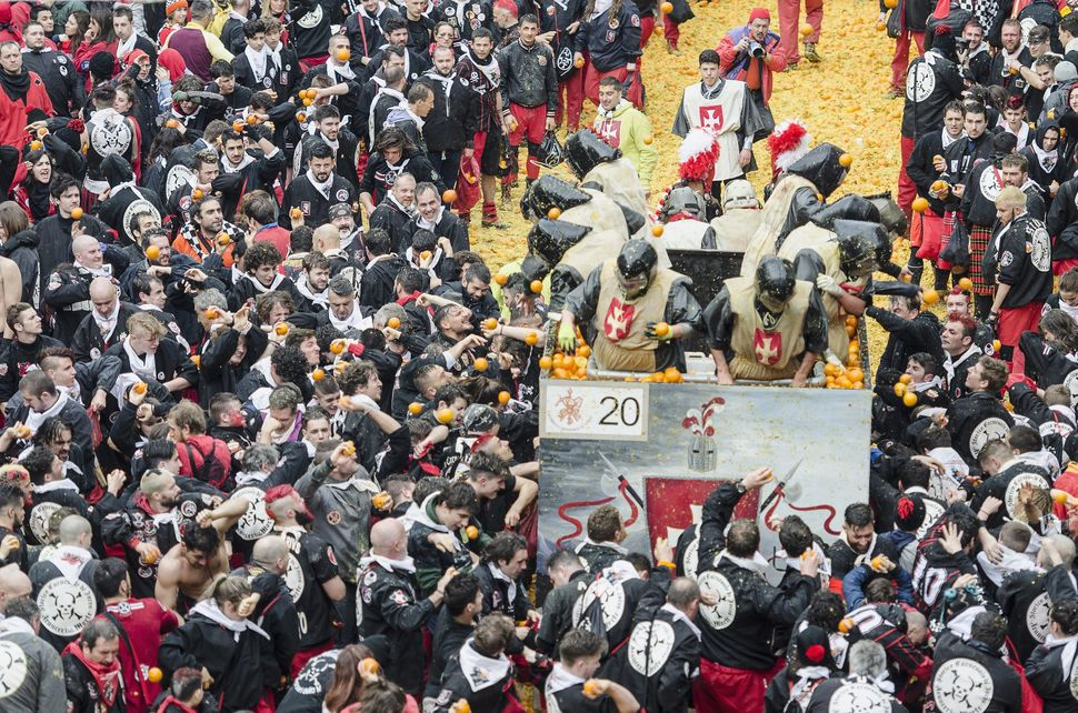 The tradition of organized teams throwing oranges commemorates a localrebellion against a tyrannical lord who ruled the