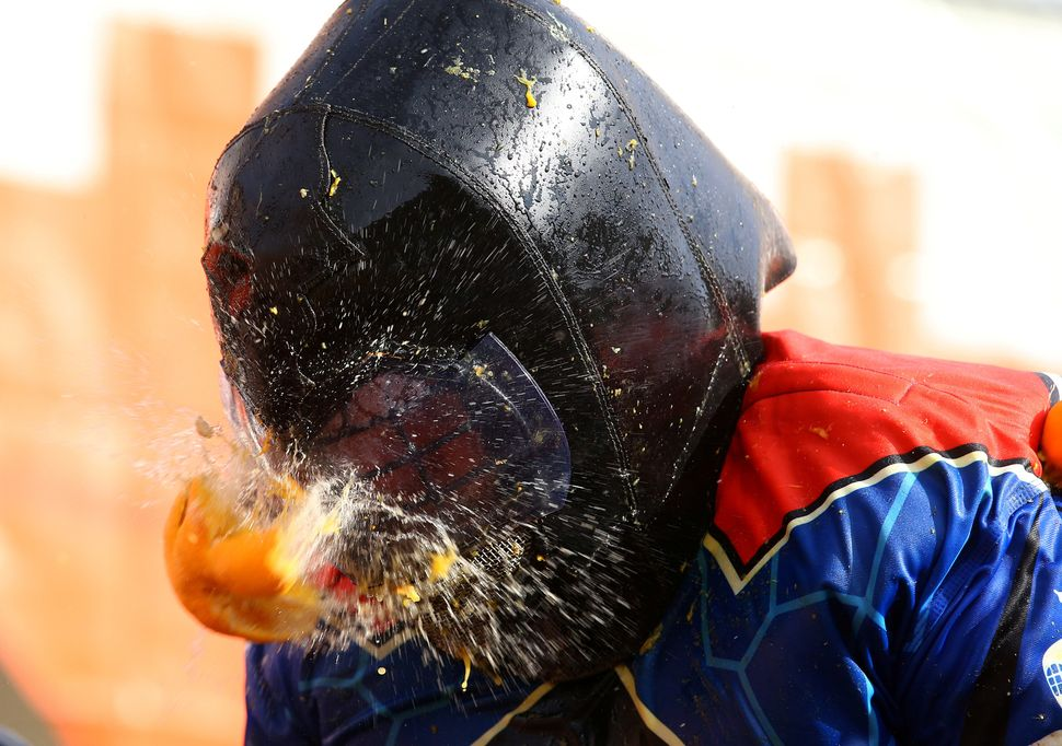 The helmet of one participantis hit by an orange.