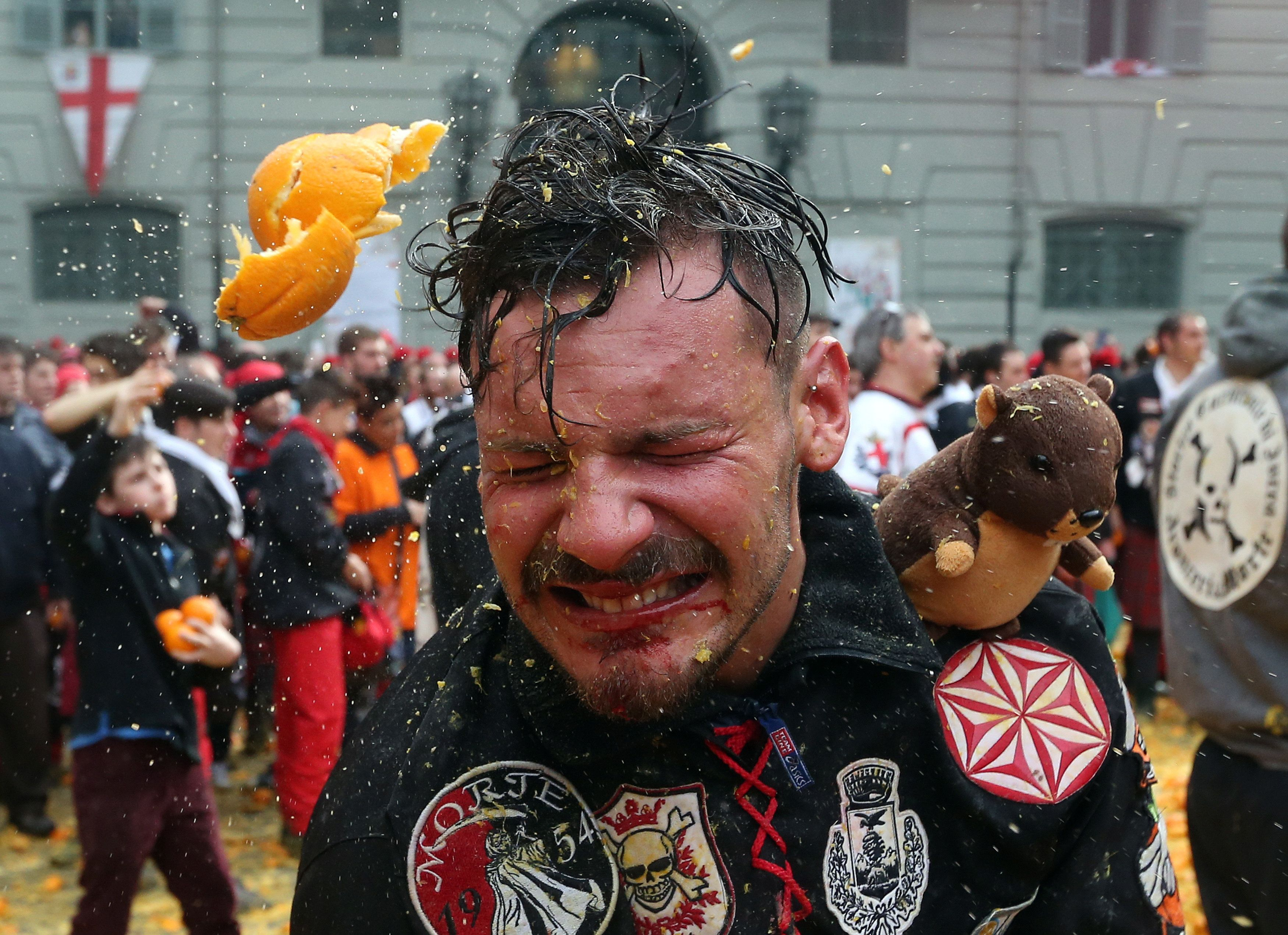 A man is hit by flying fruit during theannual Battle of the Oranges in the northern Italian town of Ivrea on Feb. 26, 2