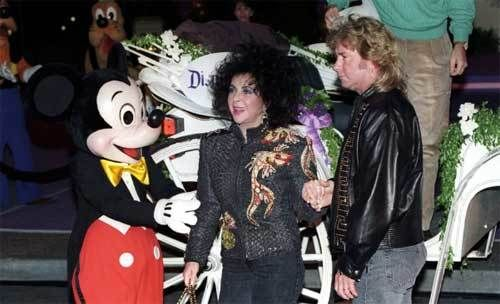 Mickey greets Elizabeth Taylor as the birthday girl, Larry Fortensky & Michael Eisner alight from their horse-drawn coach.