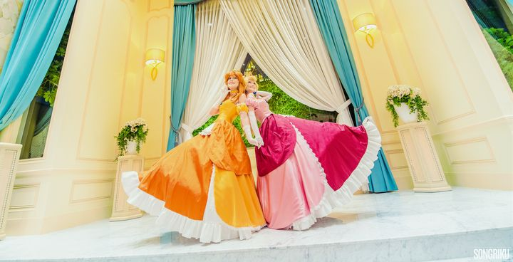 Carina cosplaying as Princess Daisy (left) and Sørine cosplaying as Princess Peach (right) from Super Mario.