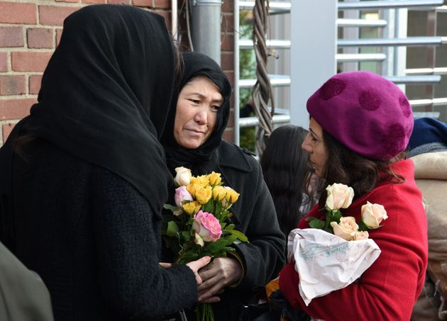 Refugees from Iran hold flowers during a demonstration against violence in Cologne, Germany, on...