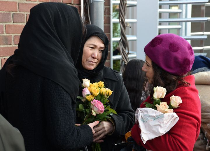 Refugees from Iran hold flowers during a demonstration against violence in Cologne, Germany, on Jan. 22, 2016.