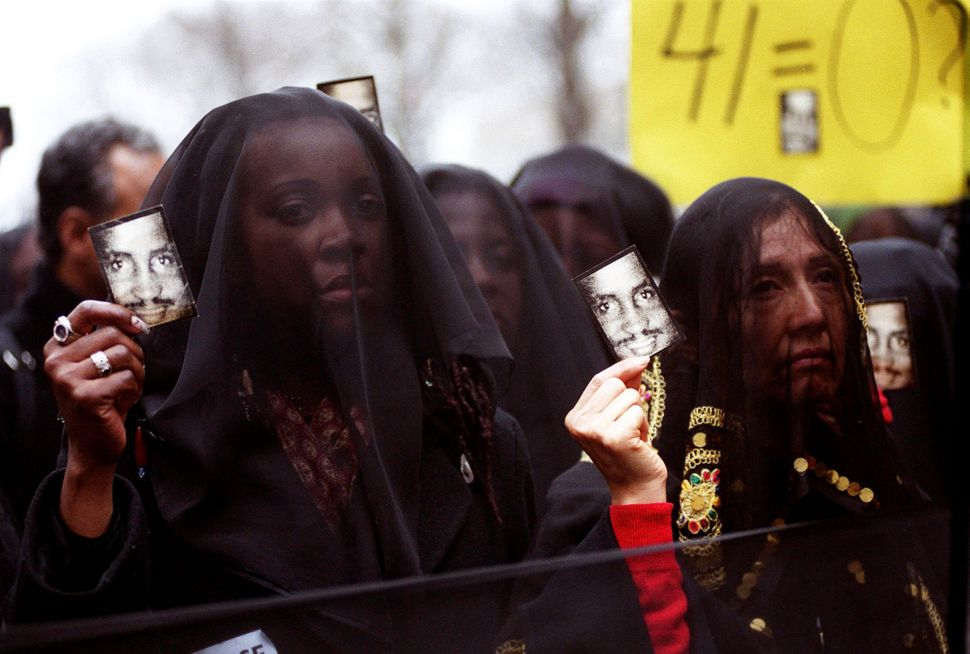 "A group called ""Women in Mourning and Outrage"" hold up photographs of Amadou Diallo during a rally in front of the United Nat"