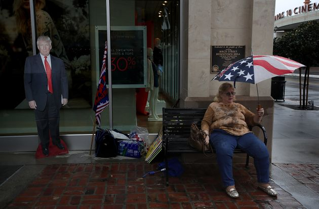A Trump supporter with a cardboard cutout of the president sits on a bench at a rainy Brea, California,