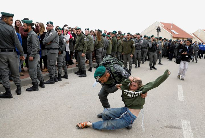 Israeli forces evict residents from several homes in the Israeli settlement of Ofra.