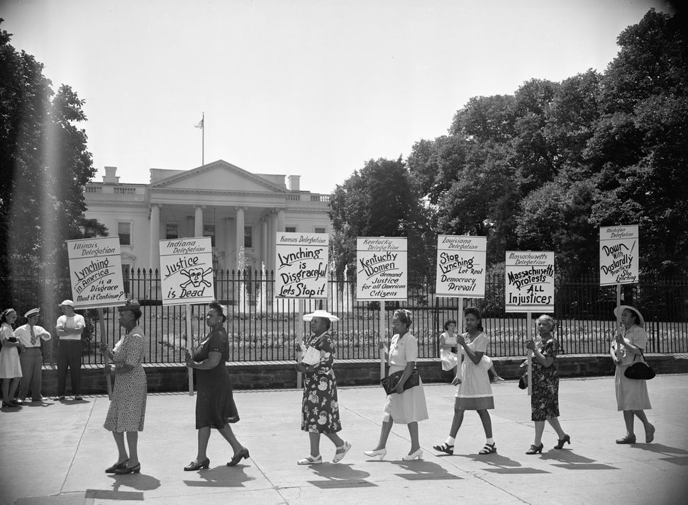 Negro delegates from several states parade with signs in front of the White House to protest the mob slaying of four negroes