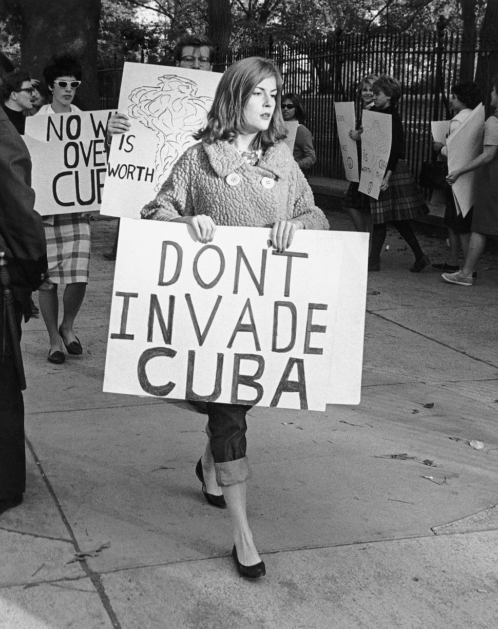 Picture shows people picketing outside of the White House in protest of the US involvement with Cuba. The woman in the foregr