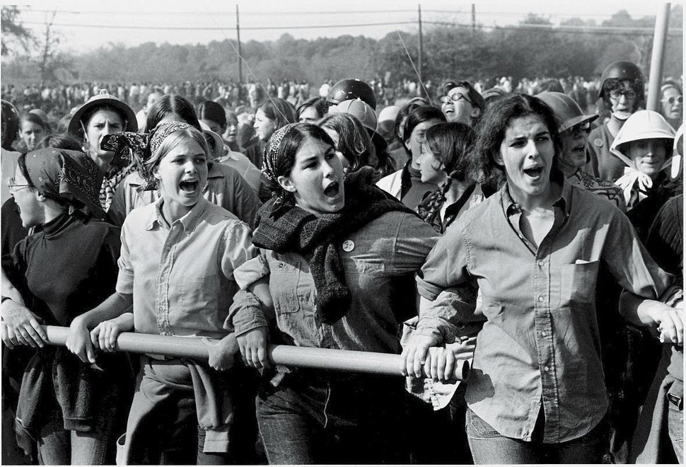 A group of young women have arms interlocked as they hold a metal pipe and protest the Vietnam War at Fort Dix, a major trans