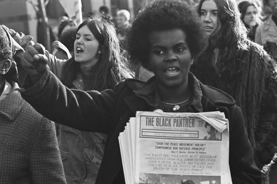 A woman at a rally in support of the Black Panthers, holding copies of The Black Panther newspaper, New Haven, CT, November,