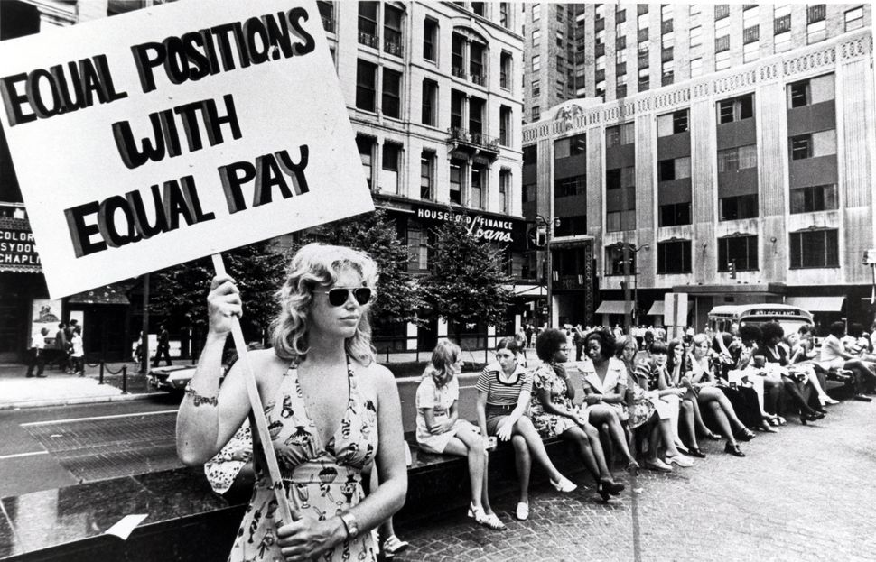 A lone woman stands on a corner protesting unequal pay for women in an unidentified section of Cincinnati, Ohio, circa 1970s.