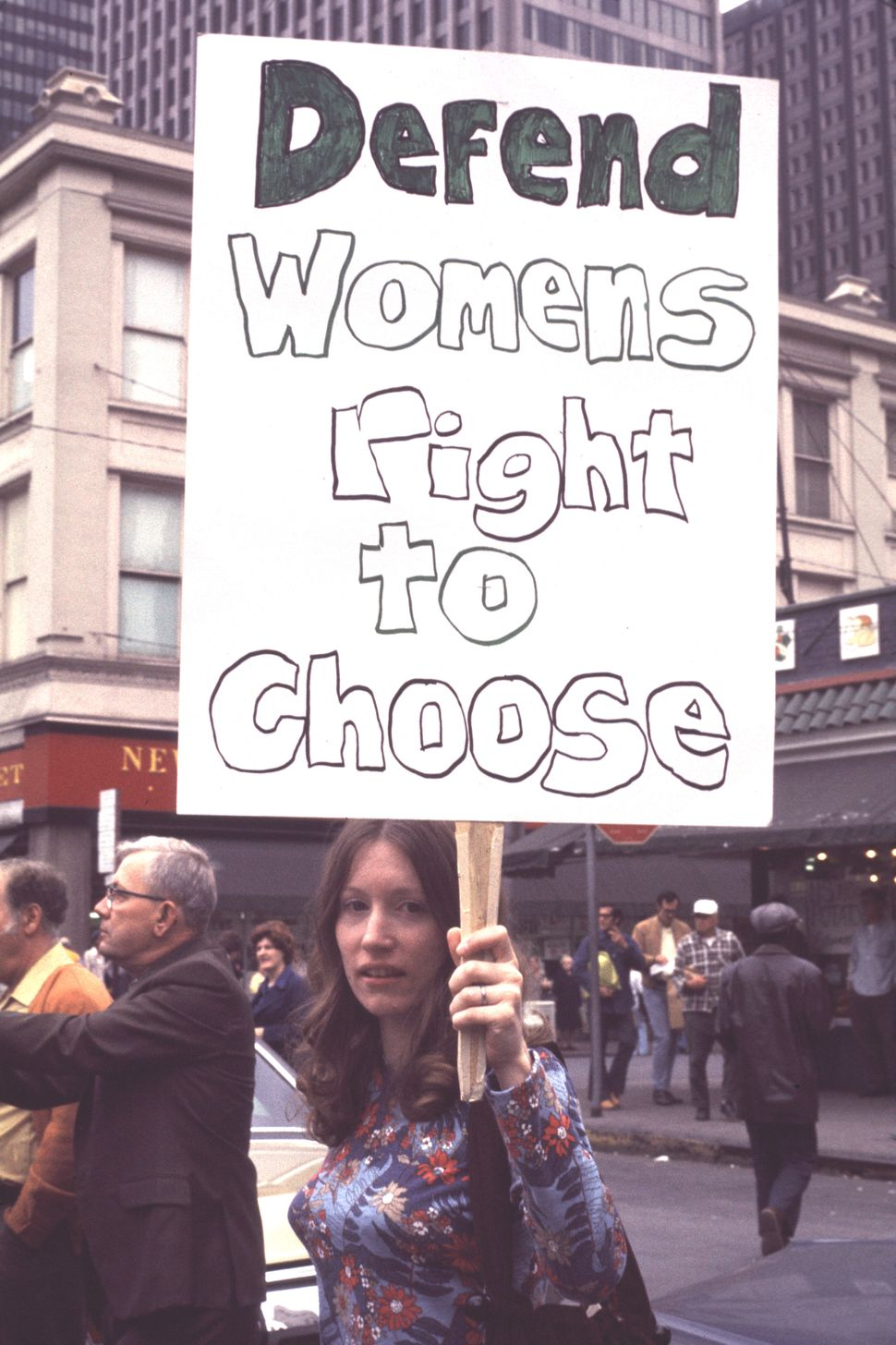 A woman at a 1974 reproductive rights march in Pittsburgh, PA holds a sign reading 'Defend Women's Right To Choose'.