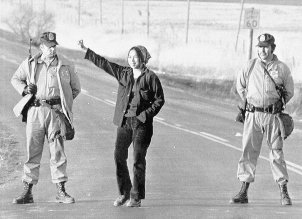 U.S. Marshals standing roadblock duty on the access road to Wounded Knee on March 1, 1973, watch as a Native American woman g