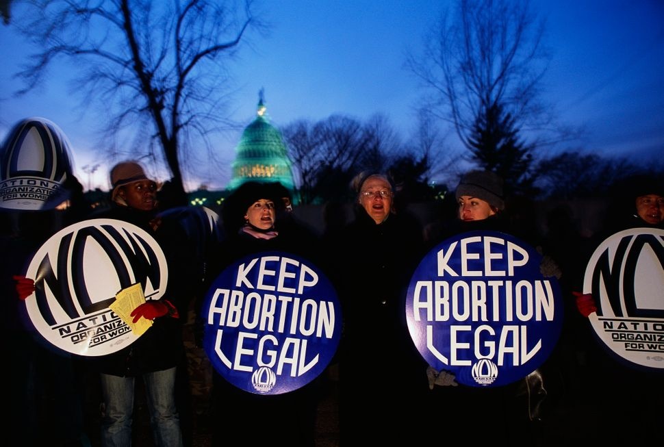 Pro-abortion activists holding signs stand together in Washington, DC in front of the Supreme Court Building on Jan, 22, 2003