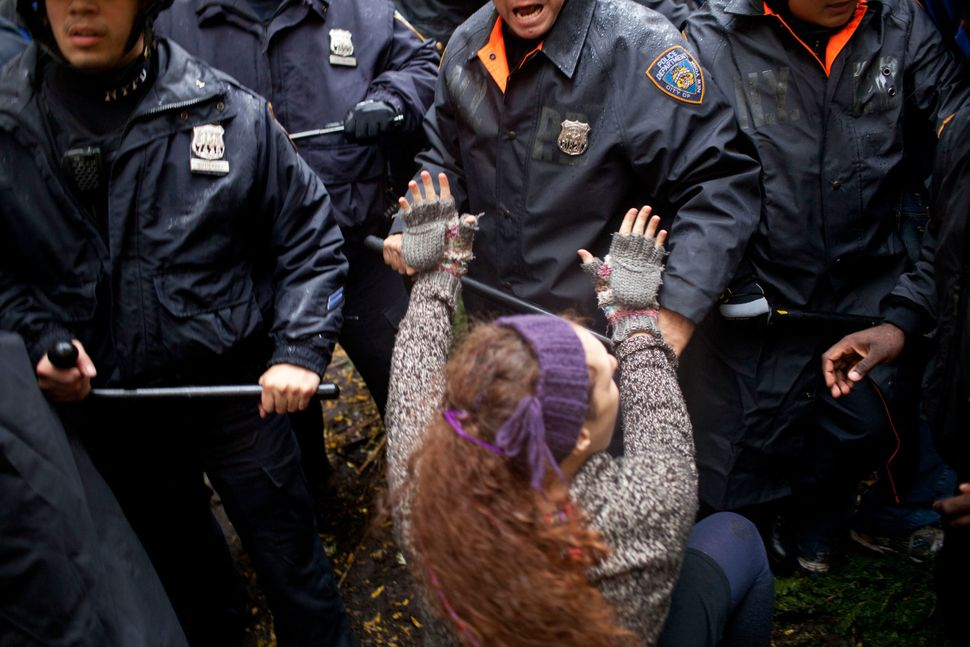 A woman puts her hands up in defense during a fight between police and protestors affiliated with Occupy Wall Street in Zucco