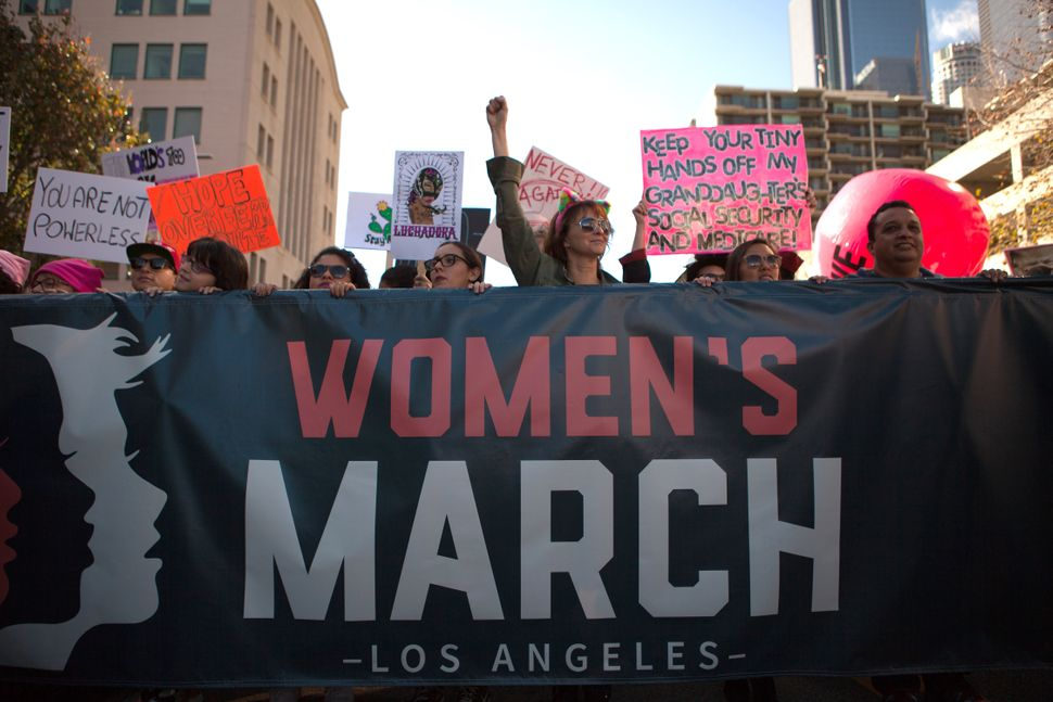 Demonstrators hold a signs and a banner while marching during the Women's March of Los Angeles in Los Angeles, California, U.