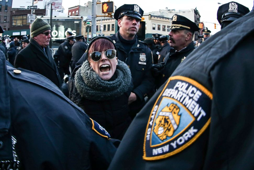 A woman is arrested by police officers during a demonstration to protest against President Donald Trump's Executive Order ban