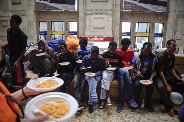 Migrants from Eritrea eat a meal they received at a Milan train station in 2015.