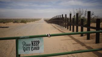 A sign is displayed on a gate near a border fence that separates the U.S. and Mexico in Santa Teresa, New Mexico, U.S., on Friday, Feb. 17, 2017. The Trump administration outlined a sweeping crackdown on undocumented immigrants Tuesday, pledging to hire 15,000 more border patrol and immigration agents and to begin building a wall on the Mexican border to enact executive orders signed by the president on Jan. 25. Photographer: Luke Sharrett/Bloomberg via Getty Images