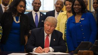 US President Donald Trump (C) signs an executive order to bolster historically black colleges and universities (HBCUs) in the Oval Office of the White House in Washington, DC, February 28, 2017. / AFP / JIM WATSON        (Photo credit should read JIM WATSON/AFP/Getty Images)