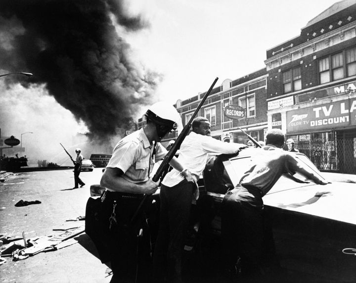 A police officers searches African-American men amid the turmoil of a Detroit street on July 25, 1967.