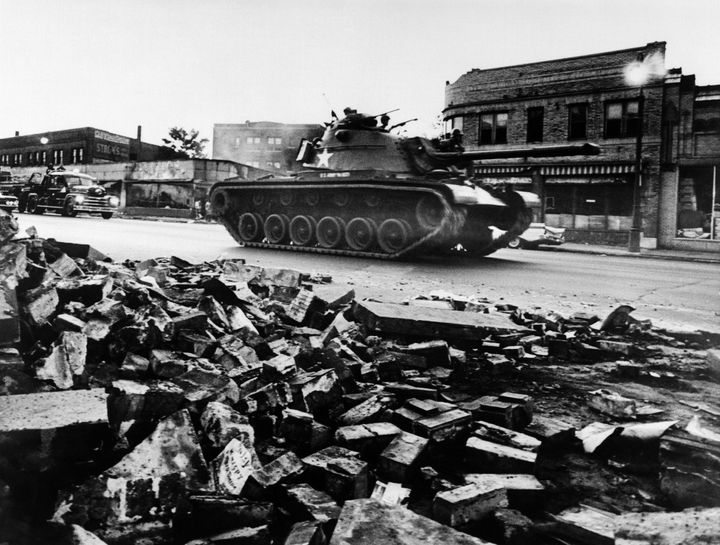 A tank patrols a devastated Detroit street on July 25, 1967.