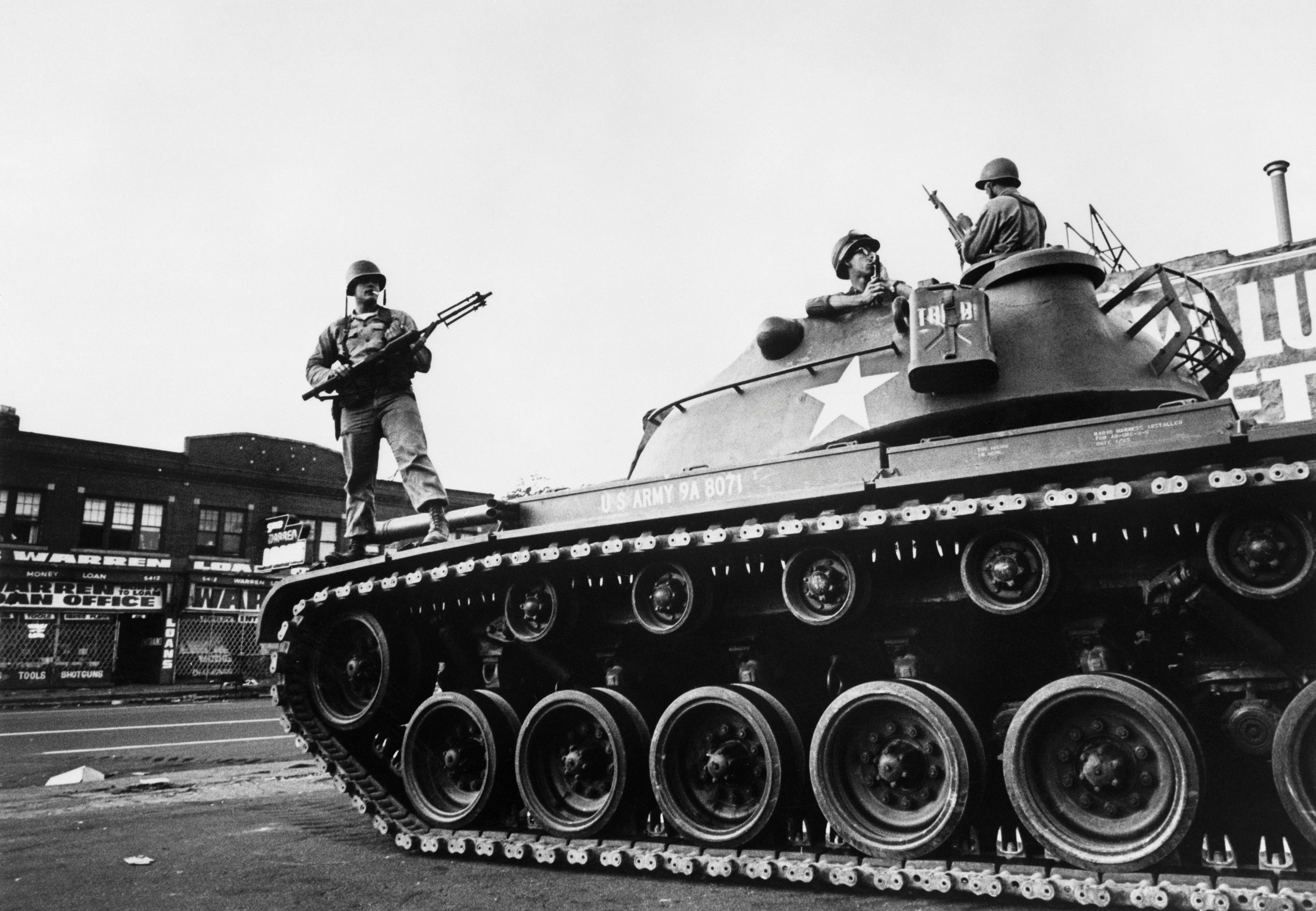 Federal soldiers stand guard on a tank in a Detroit street on July 25, 1967 during riots that erupted in Detroit following a police operation. / AFP / AFP FILES / -        (Photo credit should read -/AFP/Getty Images)
