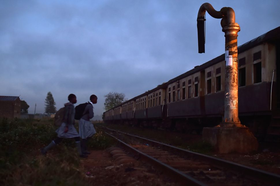 Two school girls walk towards a commuter train in Kikuyu, Kenya, on September 13, 2016. The railway in Kenya has a long histo