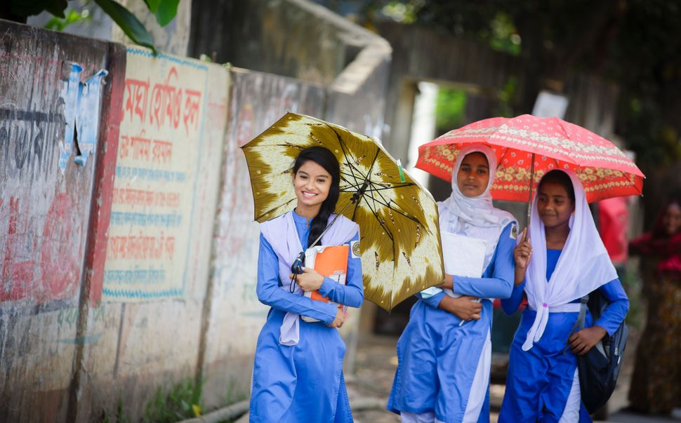 Savar, Bangladesh - April 13: Girls in school uniform walking along a road after school on April 13, 2016 in Savar, Banglades