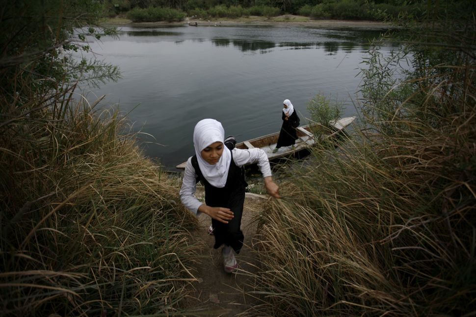 An Iraqi school girl walks up the bank of a river after crossing the waterway on a small wooden boat in the district of Al-Mi