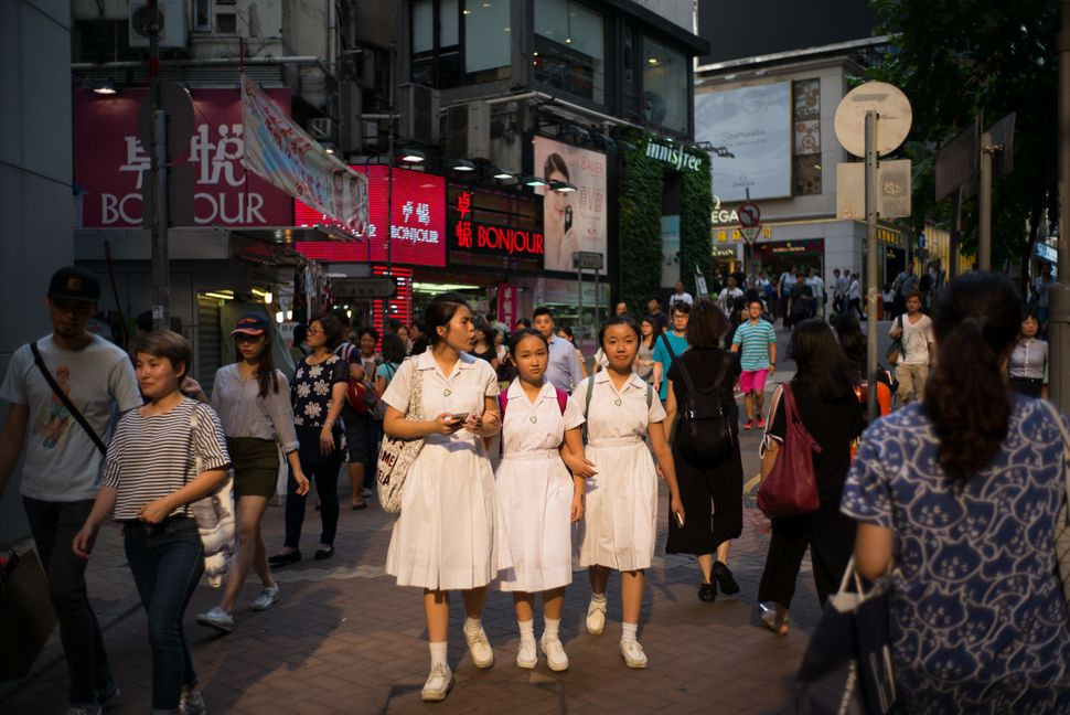 School students walk down a street in Hong Kong on July 4, 2016.