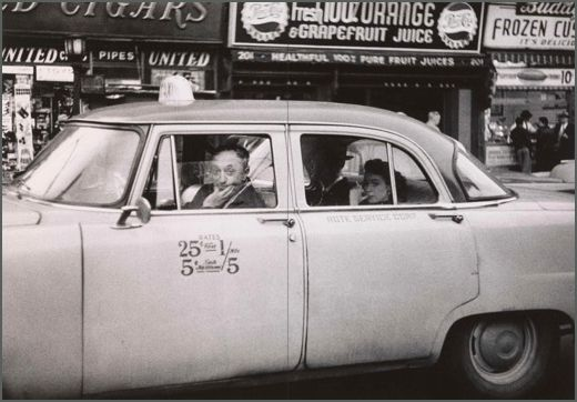 Taxicab driver at the wheel with two passengers, N.Y.C., 1956.