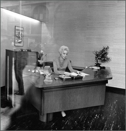 Blonde receptionist behind a picture window, N.Y.C., 1962.