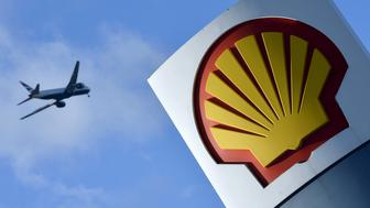 A passenger plane flies over a Shell logo at a petrol station in west London, in this January 29, 2015 file photo. Royal Dutch Shell, Europe's largest oil company, reported its lowest annual income in at least 13 years on February 4, 2016 as slumping oil prices hit profits. REUTERS/Toby Melville/Files      TPX IMAGES OF THE DAY
