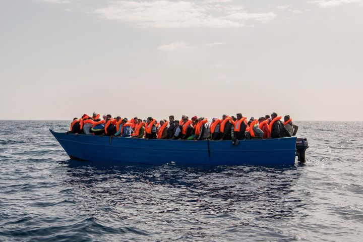 Migrants and refugees are assisted by members of the Spanish NGO Proactiva Open Arms as they crowd on board of a wooden boat