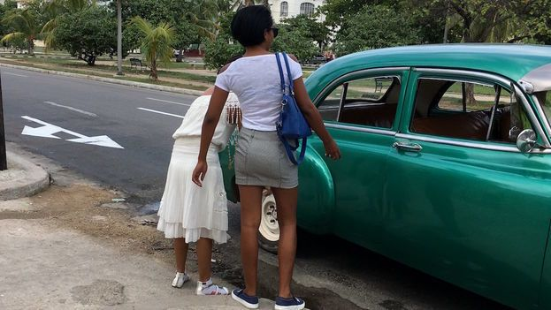 Two women board a shared taxi (almendrón) in Havana.