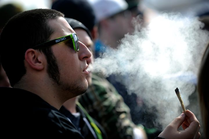 A man exhales marijuana smoke during the High Times Cannabis Cup at the Denver Mart in Denver, Colorado on April 19, 2015.