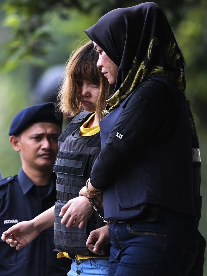 Vietnamese national Doan Thi Huong, center, 28, is escorted with a heavy police presence after a court appearance with Indone