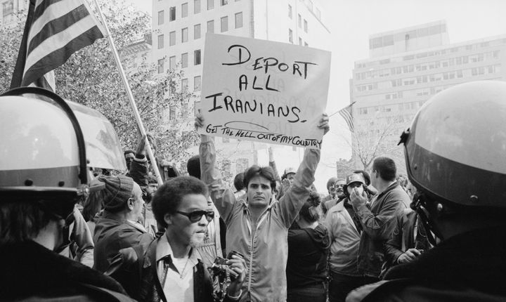 "A man holding a sign that reads ""deport all Iranians"" and ""get the hell out of my country"" during a protest of the Iran hosta"