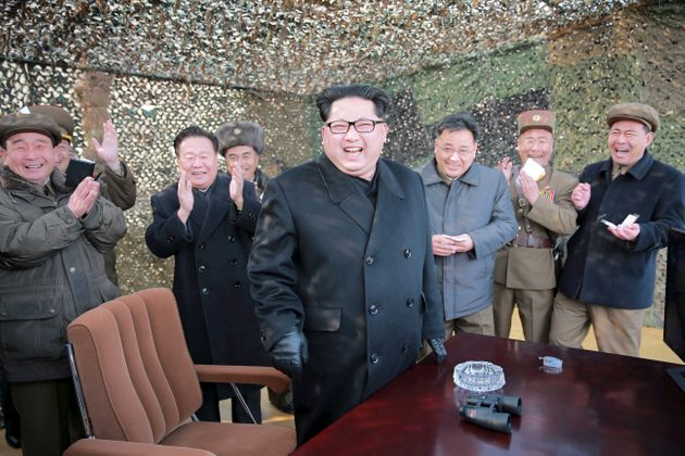North Korean leader Kim Jong Un celebratesas he guides a test fire of a new multiple launch rocket