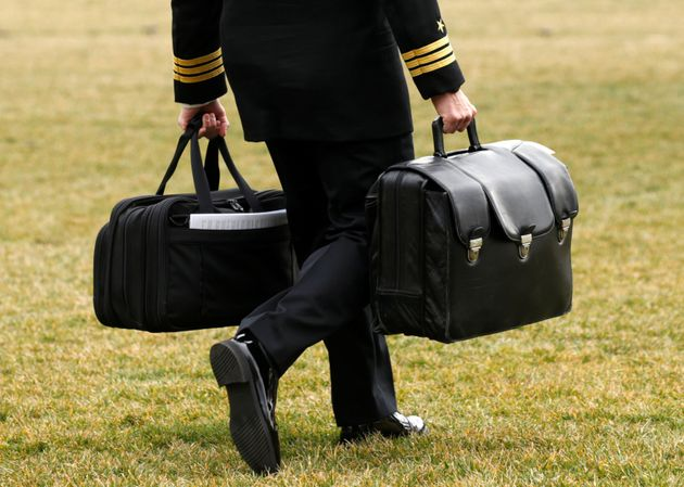 A military aide to Donald Trump carrying the so-called 'football' in February which contains the codes...