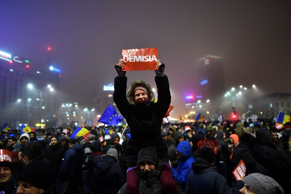 A woman holds a banner reading 'Resignation' during a protest rally against the government in Bucharest on Feb. 6, 2017. Roma