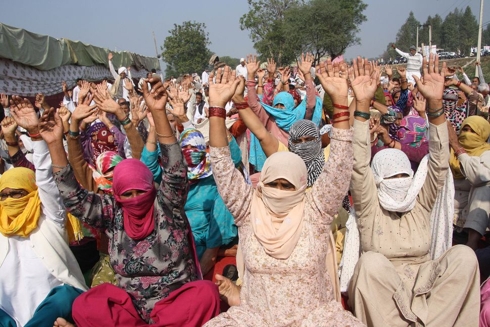 Women activists from Jat community raise their hands during their protest to demand for reservations in government jobs at Ja