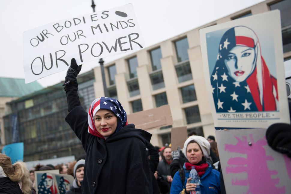 A woman wearing a USA flag as a headscarf attends a protest for women's rights and freedom in solidarity with the Women's Mar