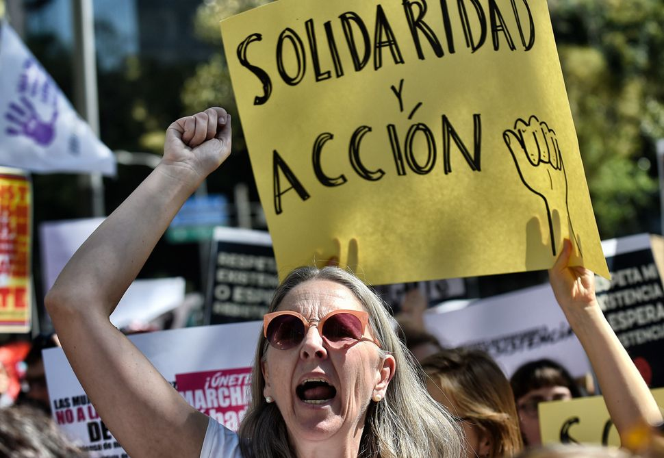 A woman holds a sign reading 'Solidarity and action' during the Women's March against President Donald Trump in Mexico City o