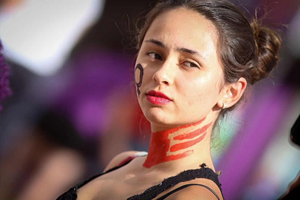 A woman with her face painted in red attends a rally to condemn a slaughter committed at the turn of the year in Campinas, Br